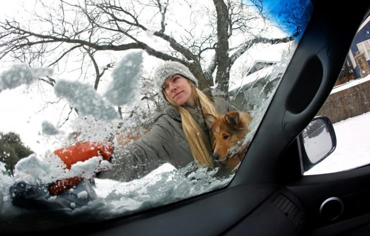 Caroline Marlett holds her dog Kit while scraping the snow off her car in Fort Worth, Texas