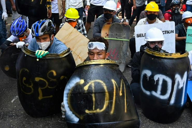 Unarmed protesers using makeshift shields against Myanmar's security forces