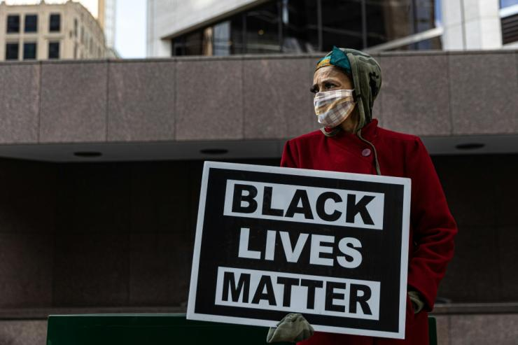 A woman protests outside the Hennepin County Government Center where the trial of former police officer Derek Chauvin is being held