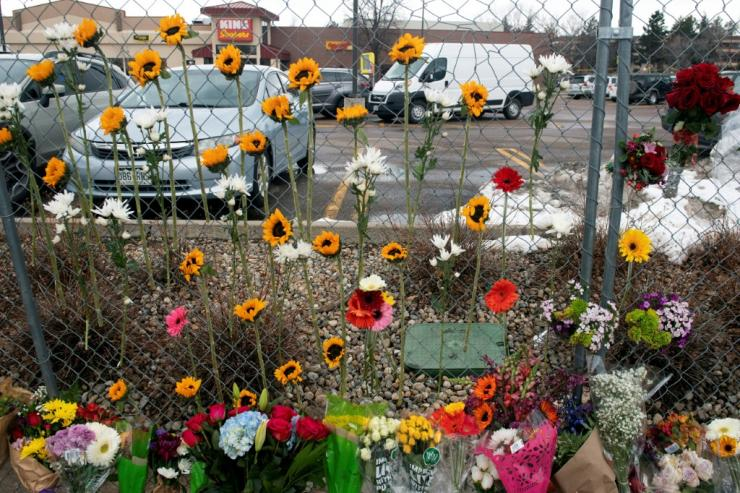 On March 23, 2021, flowers hang from a border fence outside the King Soopers grocery store in Boulder, Colorado. The day after 10 people, including police officer Boulder, died in the shootings.