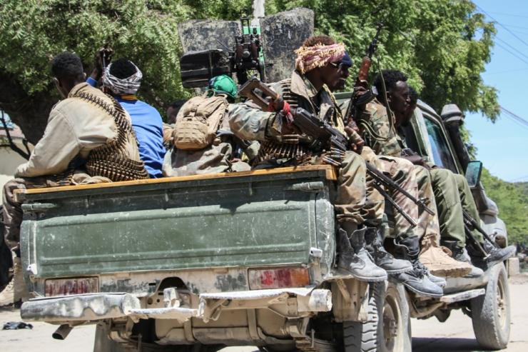Fighters in a military force supporting Somali opposition leaders patrol  a street in Mogadishu on Sunday