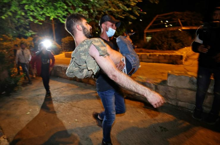 An injured Palestinian protestor is helped during clashes with Israeli police in Sheikh Jarrah in east Jerusalem