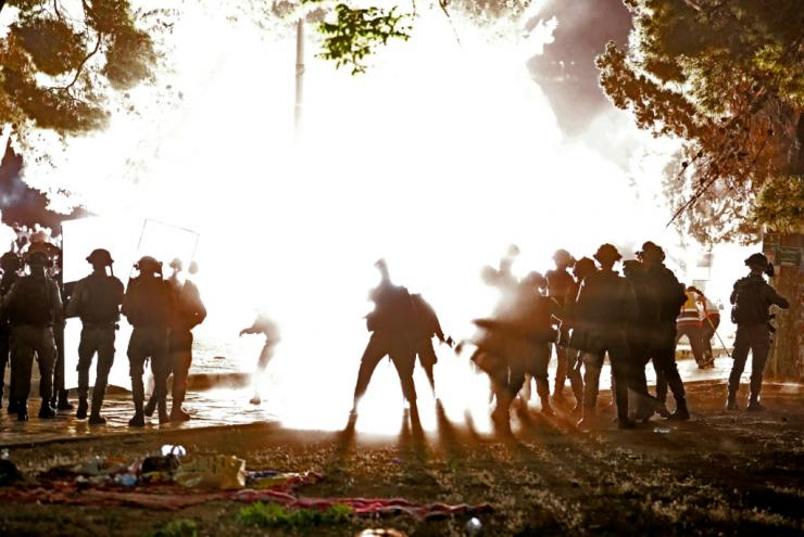 Israeli security forces form a shield as a stun grenade bursts amid clashes with Palestinian protesters at the al-Aqsa mosque compound in Jerusalem