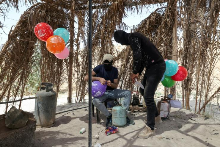 Masked Palestinian supporters of Islamic Jihad prepare incendiary balloons near Beit Lahia in Gaza City, to launch across the border fence towards Israel