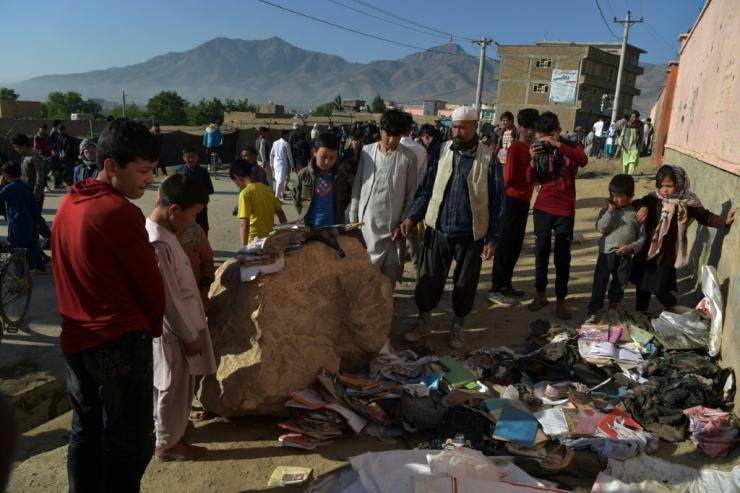 Onlookers stand next to a pile of backpacks and books of victims following multiple blasts outside a girls' school in Dasht-e-Barchi on the outskirts of Kabul