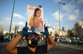 A Lebanese protester carries a photo of three-year-old Alexandra, who was fatally injured in the port explosion